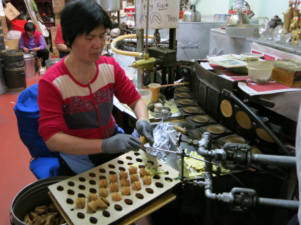 A worker folds hot wafers into fortune cookies