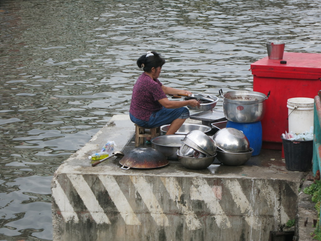 A lady washes dishes on the side of the canal