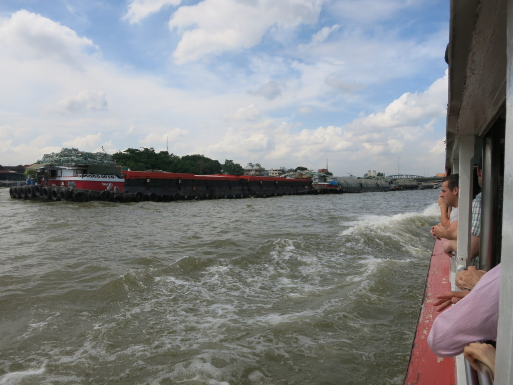 A large barge being pulled up the river
